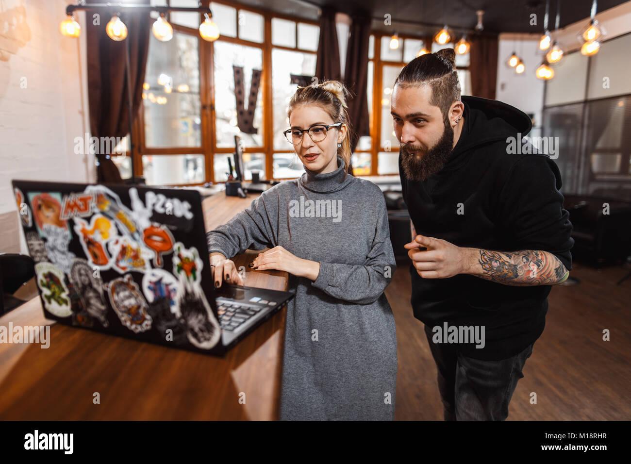 L uomo e la donna a discutere su digital portatile in ufficio creativo Immagini Stock