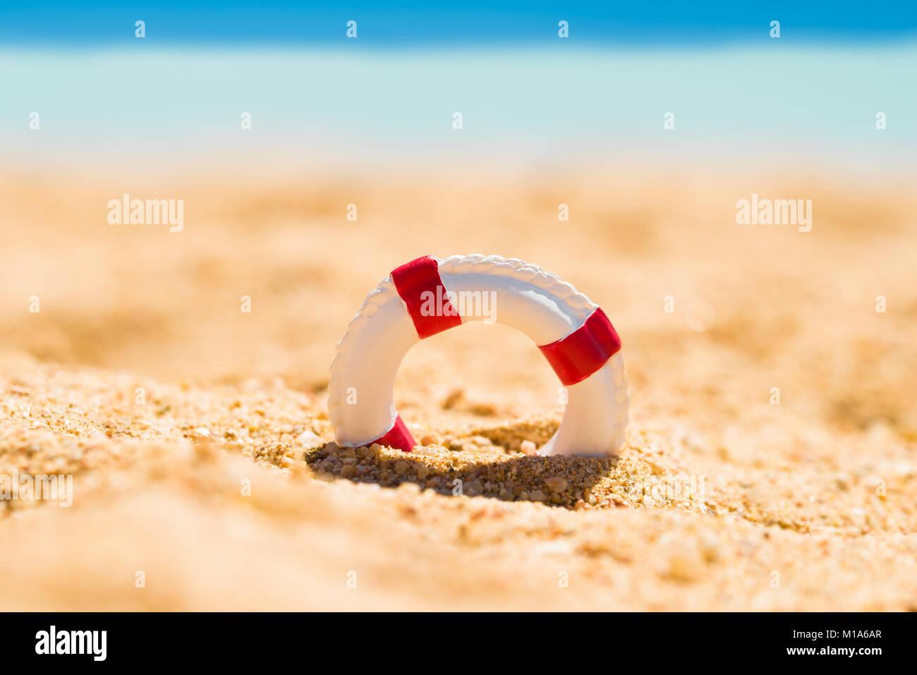 Miniatura il bianco e il rosso salvagente in sabbia in spiaggia Immagini Stock