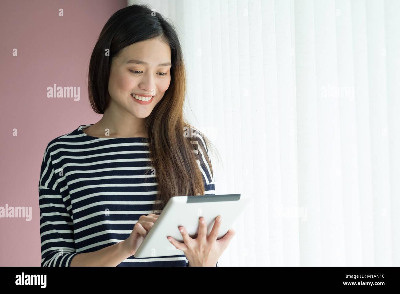 Asian business owner usura panno casuale utilizzando tablet in home office e spazio di lavoro per contattare il Immagini Stock