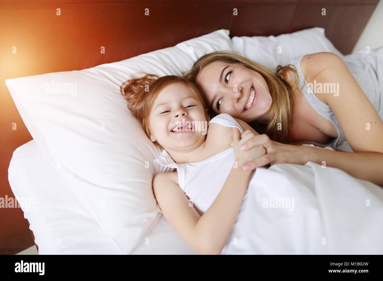 Bellezza madre abbracci piccola figlia a letto bianco con il sole ...