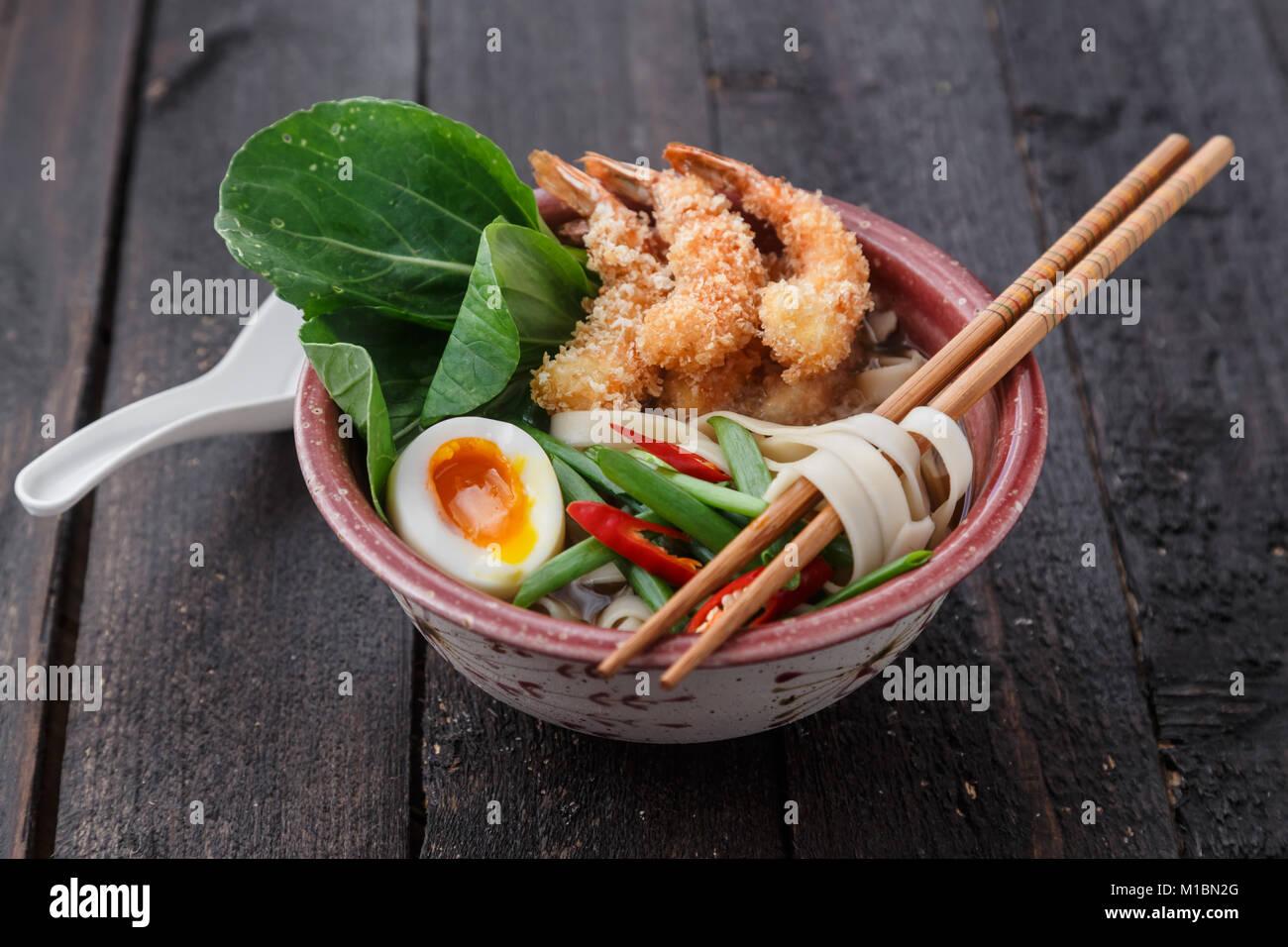 Asiatica di frutti di mare piccante zuppa di noodle con tempura di gamberi e verdi, Chiudi vista Immagini Stock