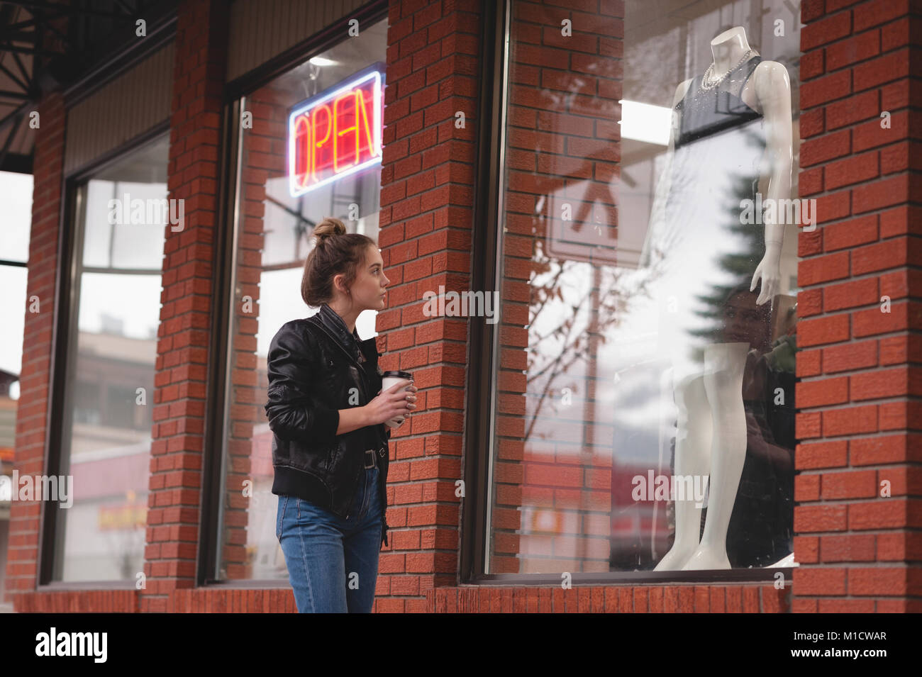 Bella donna guardando abiti sul manichino Immagini Stock