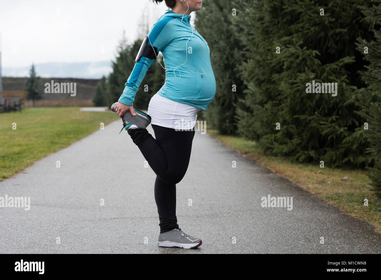 Donna incinta eseguendo stretching esercizio Immagini Stock