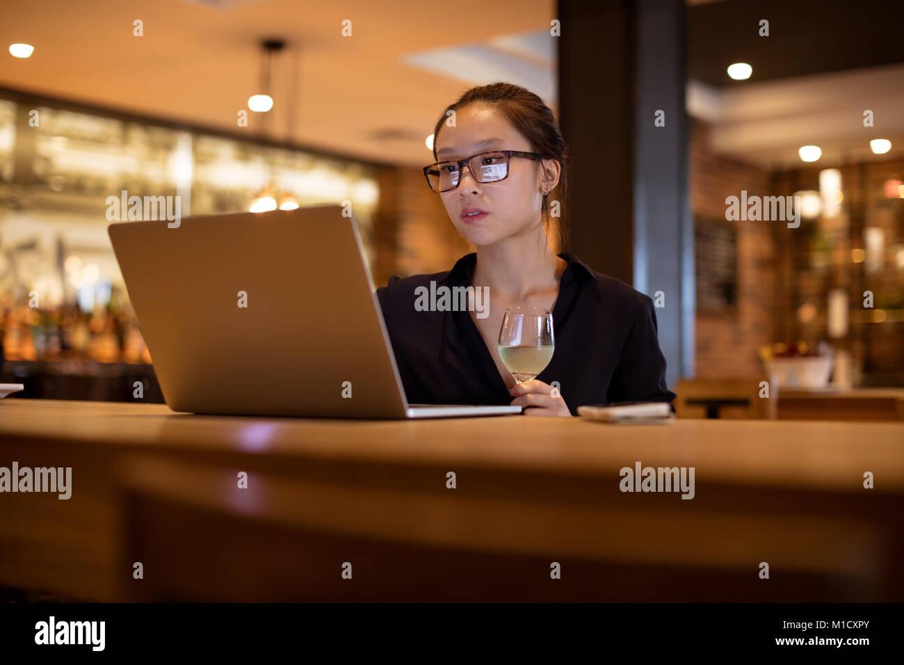Executive femmina utilizzando computer portatile mentre avente il vino Immagini Stock