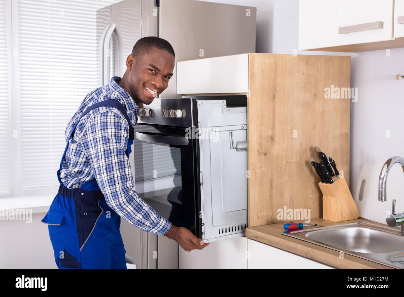 Maschio tecnico africani in generale l'installazione di forno in cucina Immagini Stock