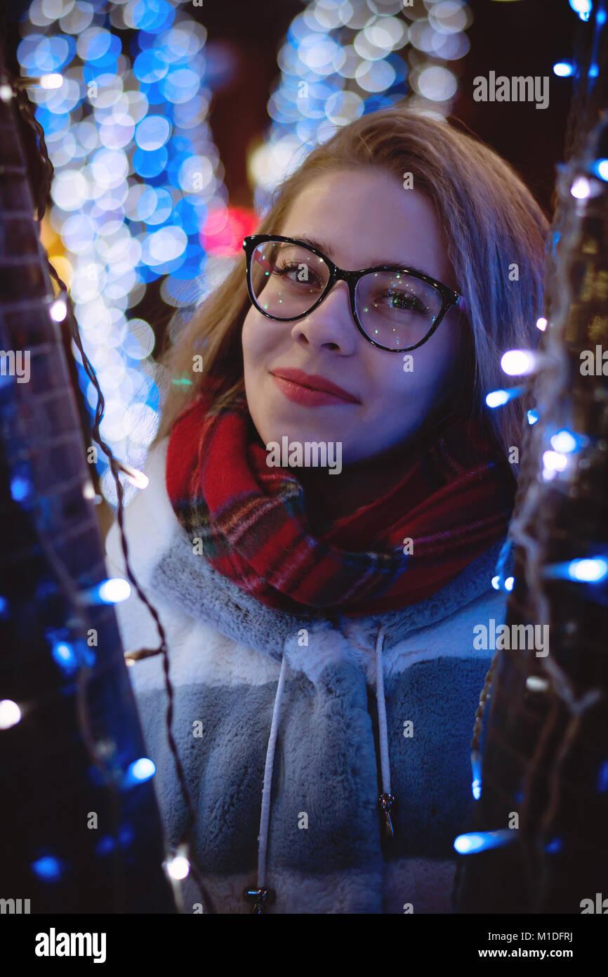 Una giovane ragazza attraente in bicchieri e una calda sciarpa passeggiate in città fiera. Sorride. Ritratto di notte tra ghirlande. Foto Stock