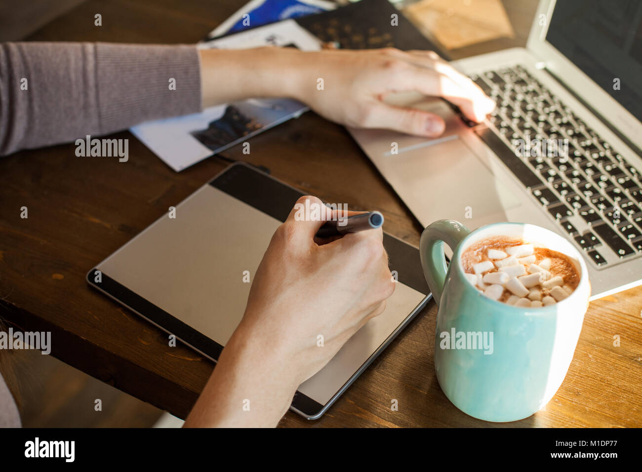 Designer con tavoletta grafica e il computer portatile presso l'ufficio domestico Immagini Stock