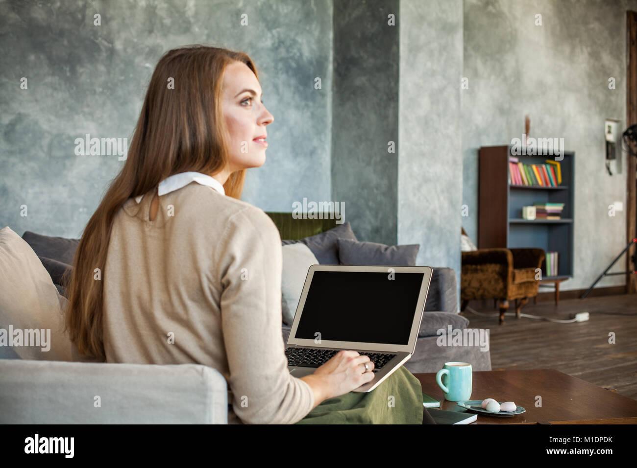 Lo schermo del laptop sulla donna sfocata e sfondo interni Immagini Stock