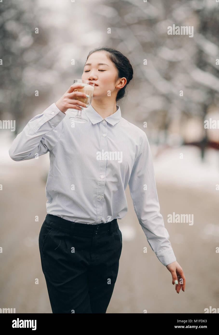 00e0c56b75 Giovane donna giapponese vestita in pantaloni neri e camicia bianca con un  bicchiere di caffè caldo