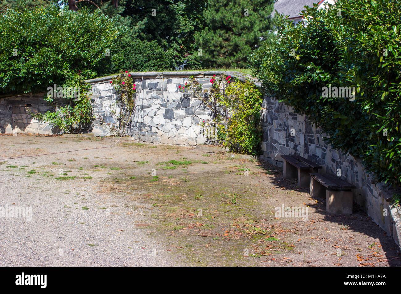 Panche In Pietra Da Giardino.Il Muro Di Pietra Nel Giardino E Coperto Con Rose Rampicanti Ci