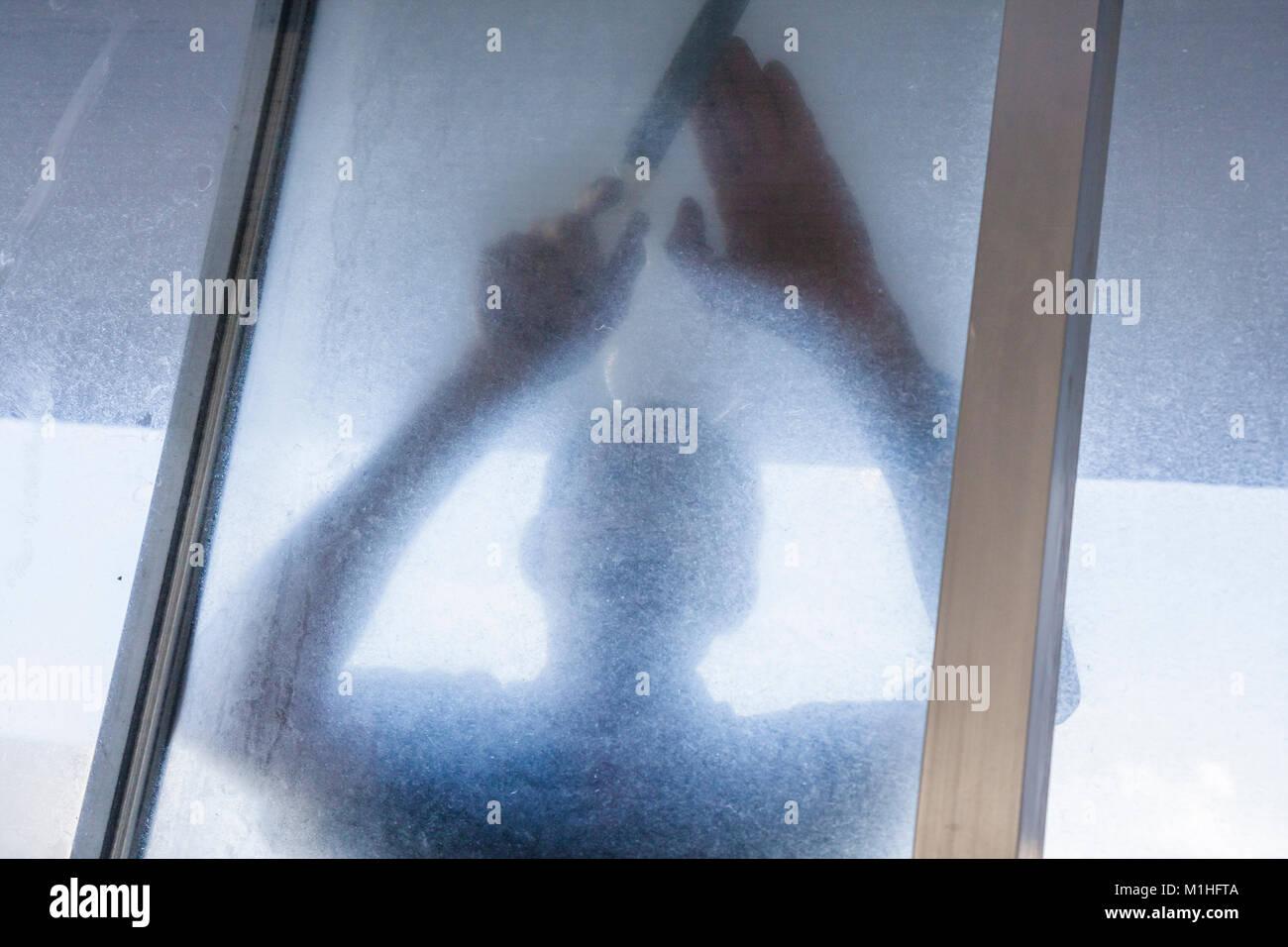 Miami Beach uomo ispanico edificio condominiale manutenzione riparazione lavoro porta a vetri scorrevole sporco Foto Stock