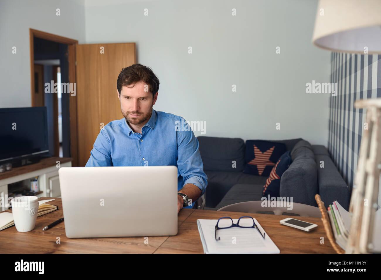 Giovane uomo che lavora da casa su un computer portatile Immagini Stock