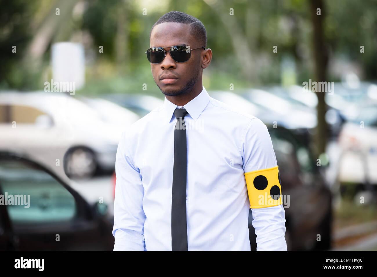Ritratto di cieco indossando giallo fascia per il braccio e gli occhiali da sole in piedi all'aperto Immagini Stock