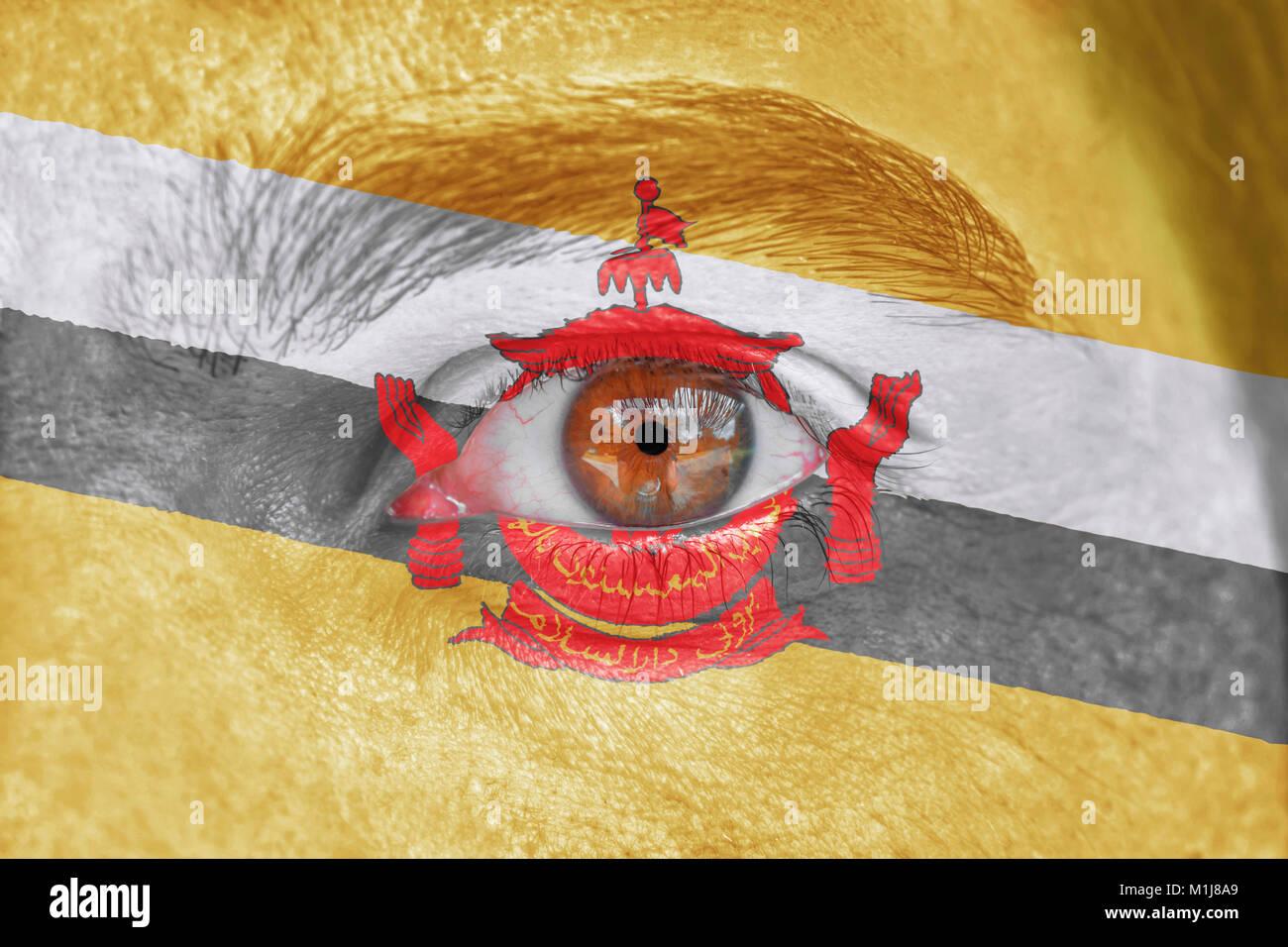 Volto umano e l'Occhio dipinto con la bandiera del Brunei Immagini Stock