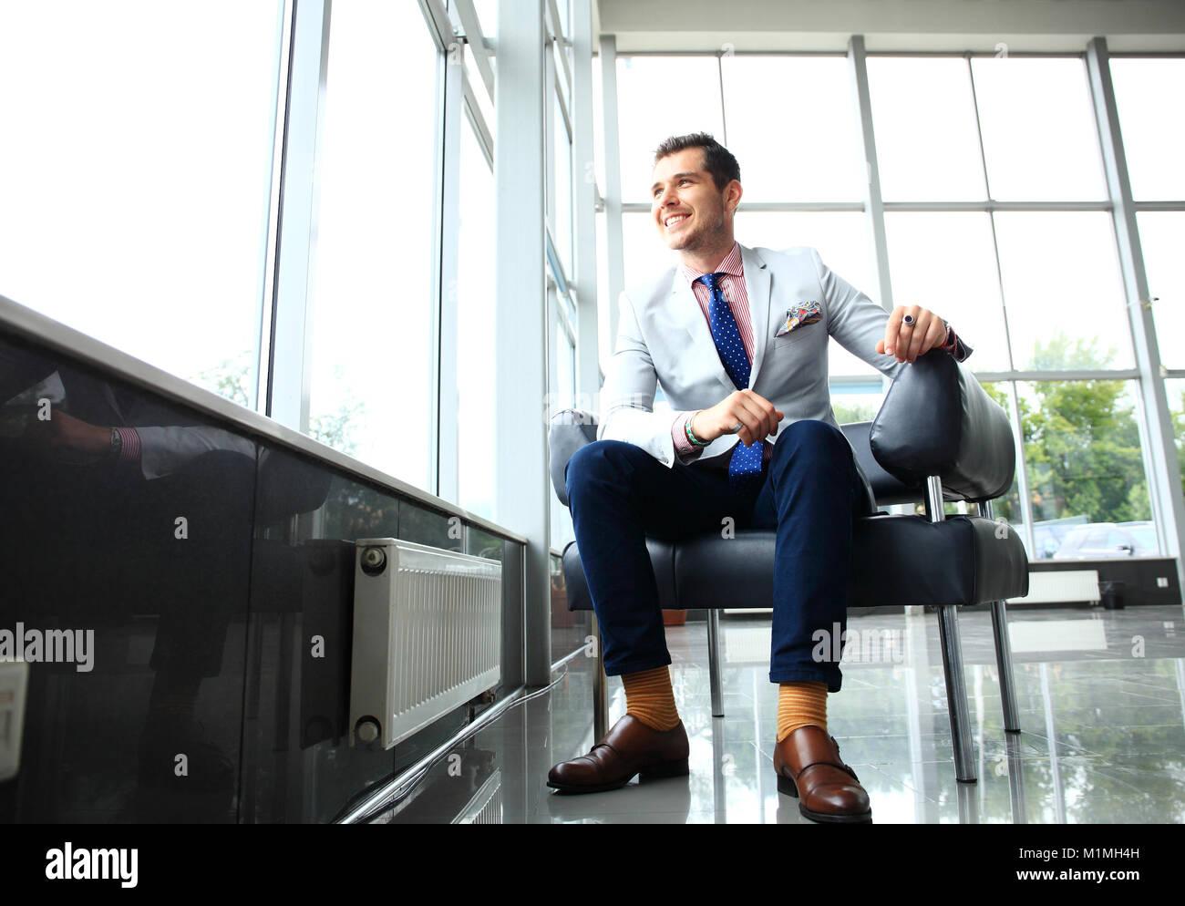 Bassa angolazione di un bel giovane imprenditore in un elegante e moderno spazio per uffici con grandi finestre. Immagini Stock
