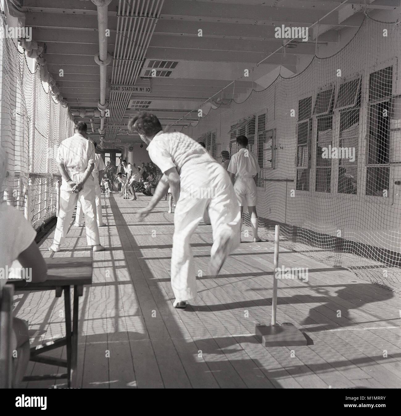 Degli anni Cinquanta, storico, maschio passeggeri ed equipaggio giocando una partita di cricket di coperta. Essi Immagini Stock