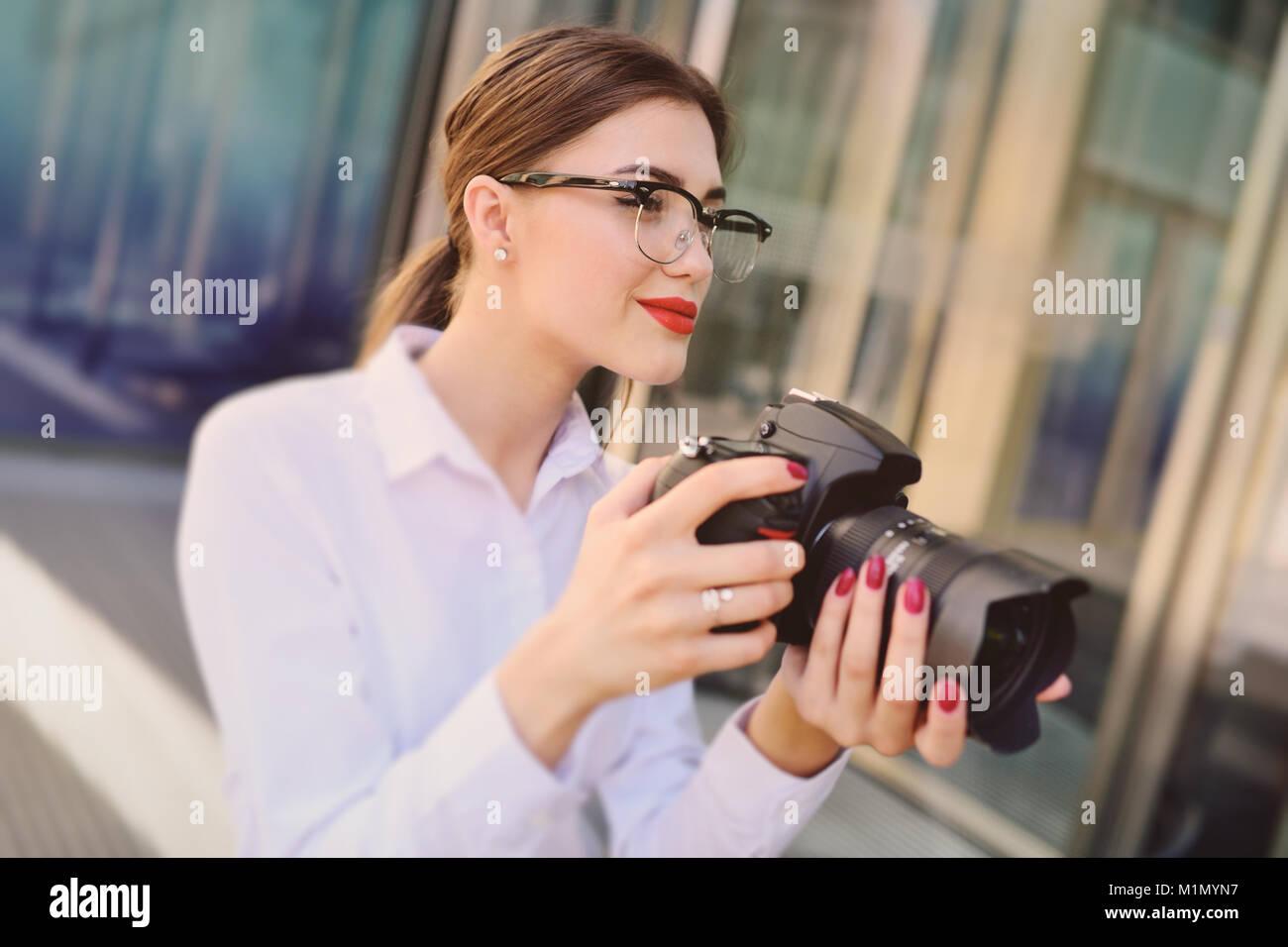 Giovane e bella ragazza in camicia bianca tenendo in mano la fotocamera preme il pulsante otturatore e guarda nel Immagini Stock