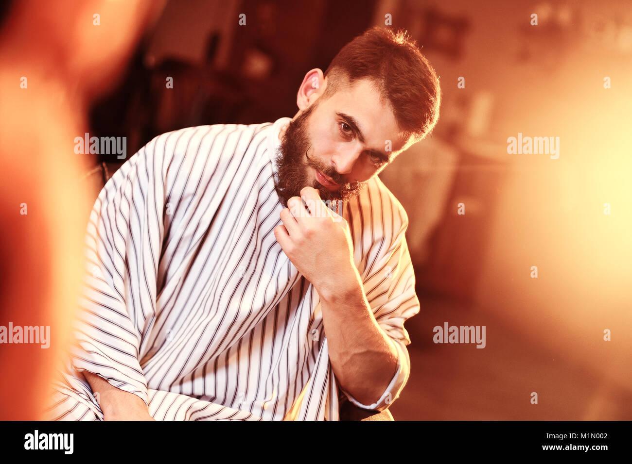 Un bel uomo coraggioso con la barba in una barberia Immagini Stock