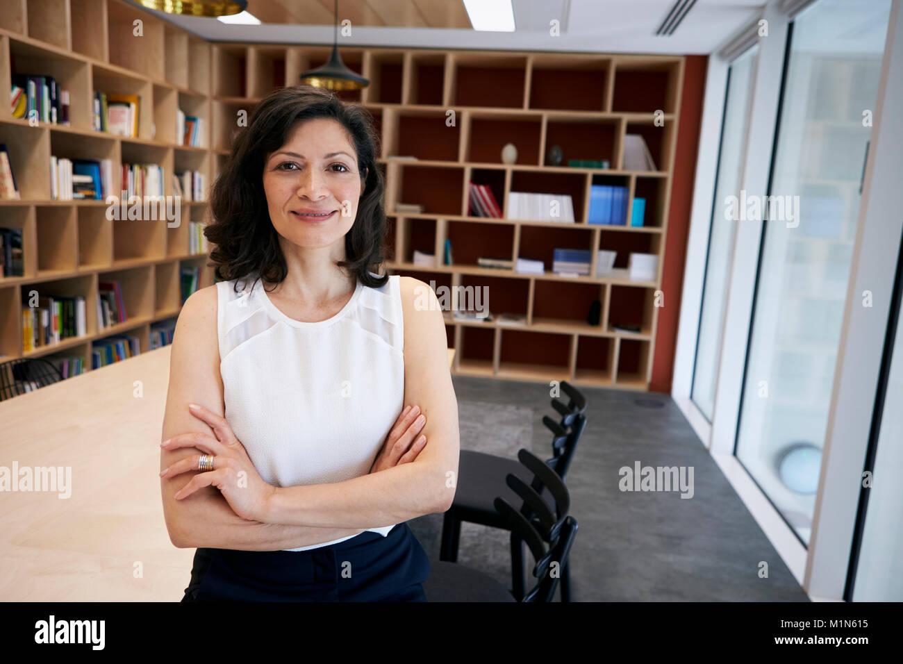 Di mezza età creativo femminile sorride alla telecamera nel suo ufficio Foto Stock