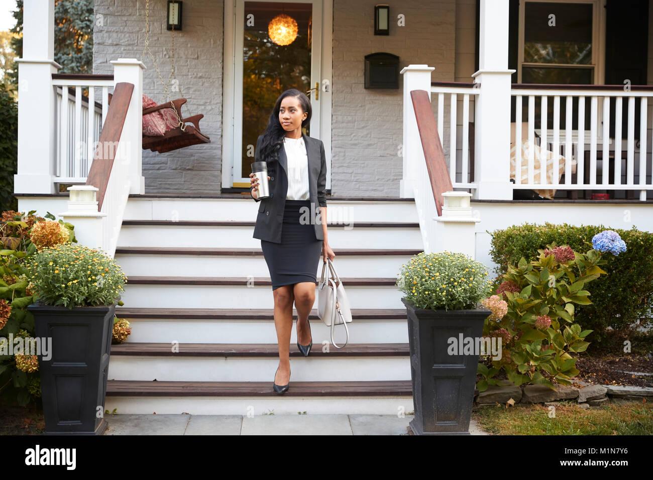 Imprenditrice con tazza di caffè lasciando casa suburbana per lavoro Immagini Stock