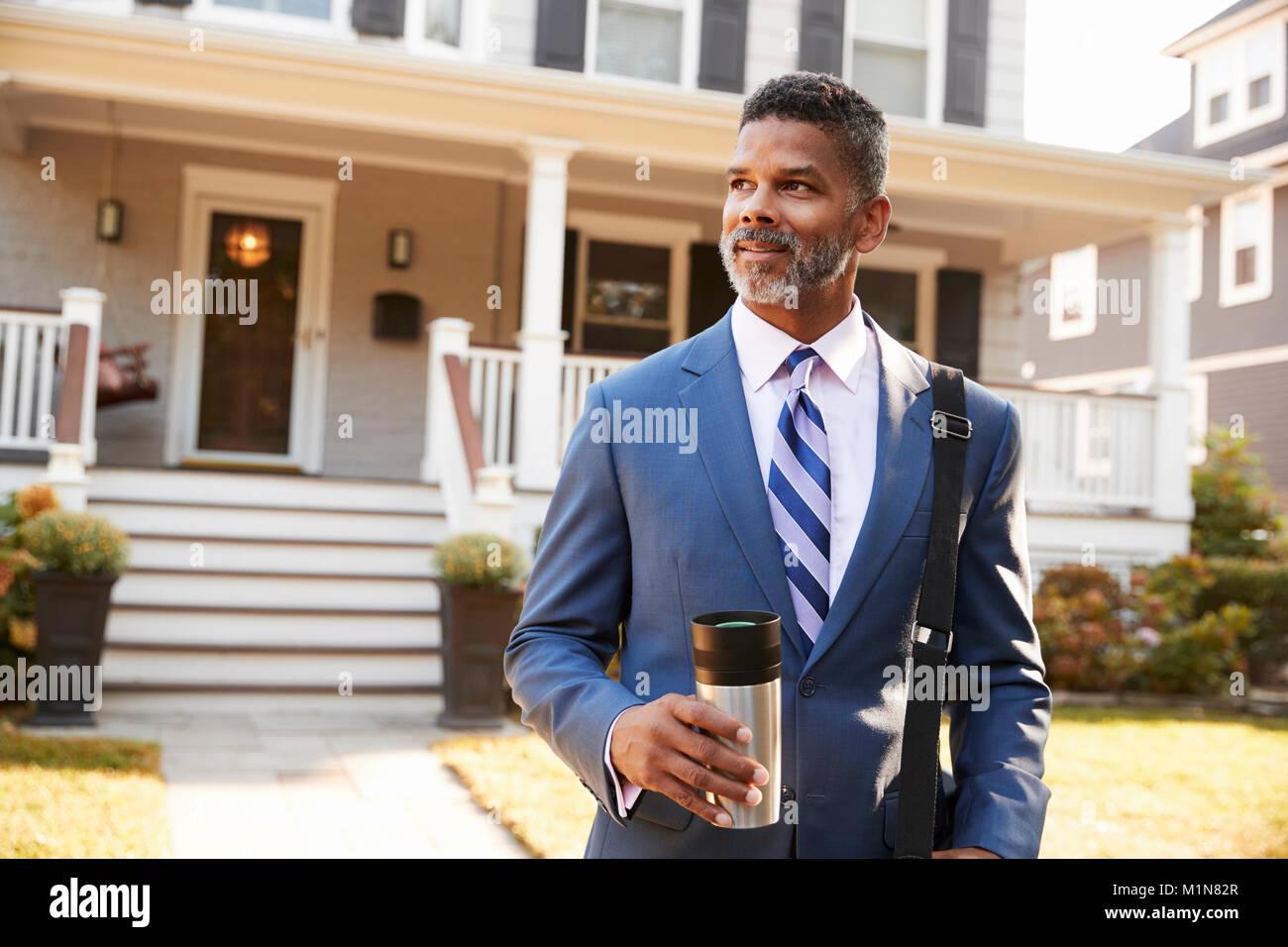 Imprenditore con tazza di caffè lasciando casa suburbana per lavoro Immagini Stock