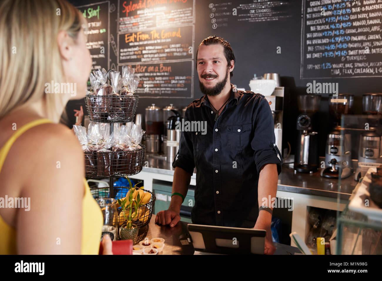 Cameriere tenendo femmina di ordine del cliente nel Coffee Shop Immagini Stock
