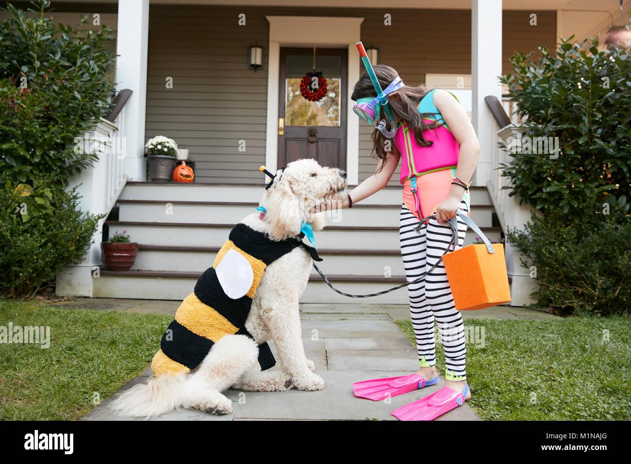Ragazza con cane indossando costumi di Halloween per il trucco o il trattamento Immagini Stock