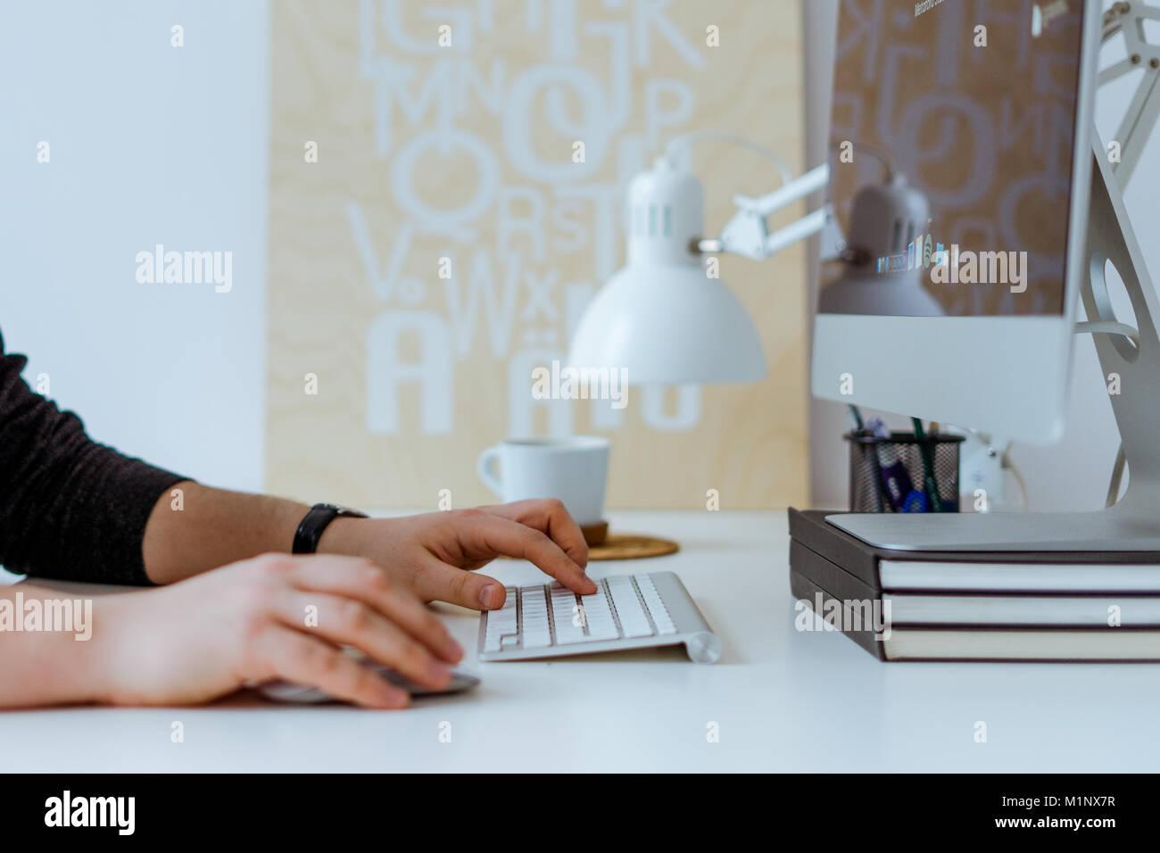 Il lavoro creativo sul computer in ufficio mentre si beve il caffè Immagini Stock