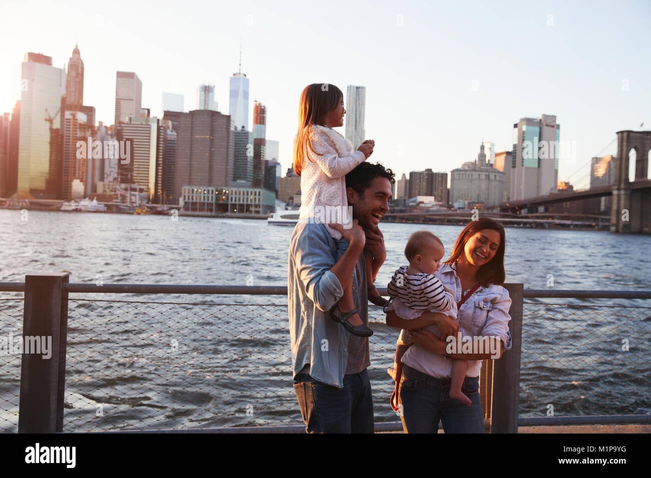 Famiglia giovane con le figlie in piedi sul Quayside, vista laterale Immagini Stock
