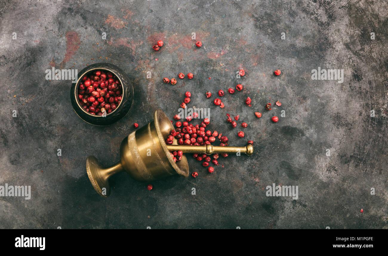 Pepe rosa semi e un mortaio di ottone su metallo arrugginito sfondo, vista dall'alto, spazio di copia Immagini Stock