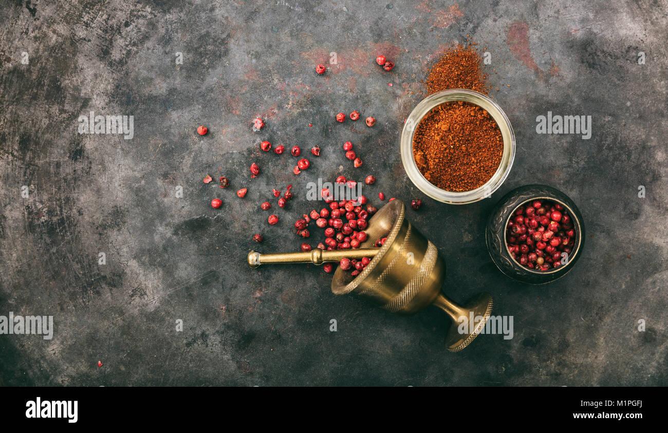 Pepe rosa semi e polvere e un mortaio di ottone su metallo arrugginito sfondo, vista dall'alto, spazio di copia Immagini Stock