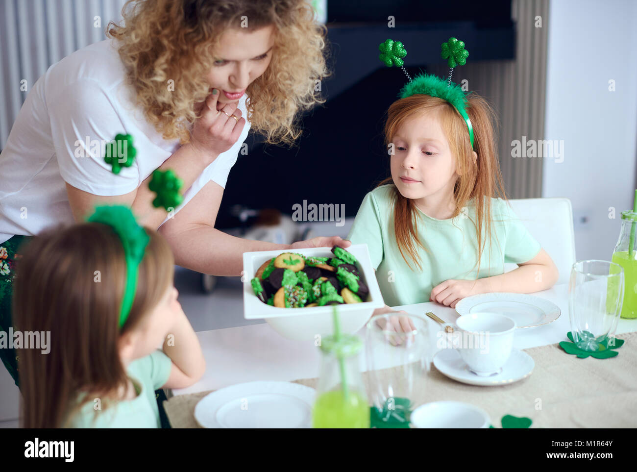 La madre dei bambini che offre gustosi biscotti Immagini Stock