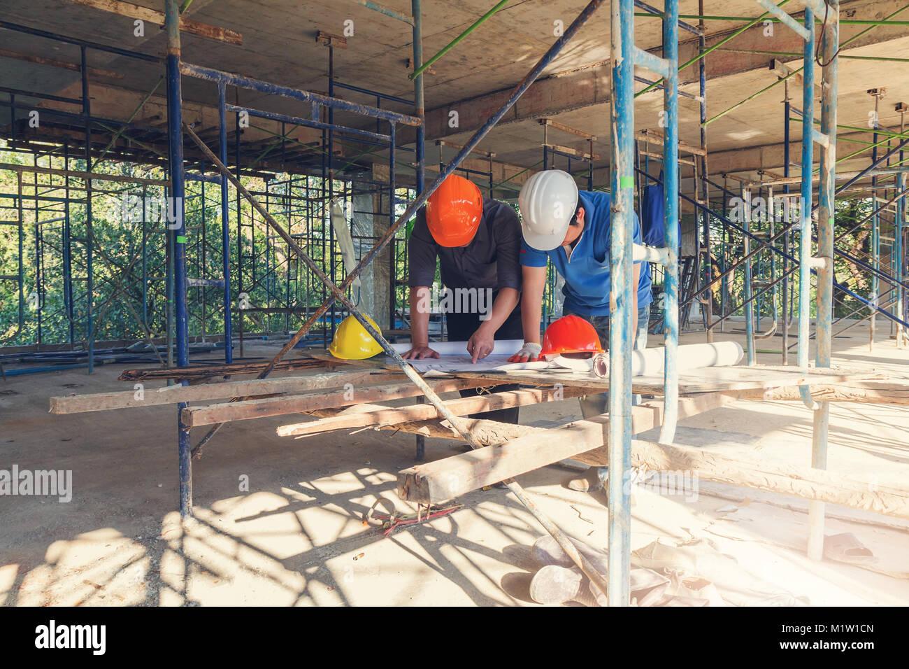 Il concetto di costruzione di ingegnere e architetto lavora al sito in costruzione con stampa blu Immagini Stock