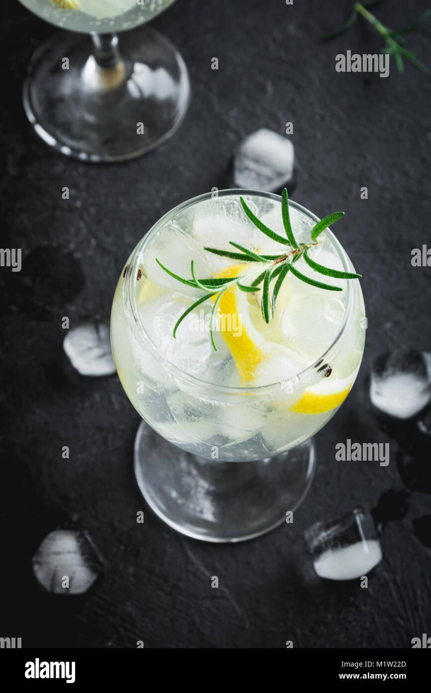 Bere alcool (gin tonic cocktail) con limone e rosmarino e su ghiaccio nero rustico tavolo di pietra, copia spazio, Immagini Stock