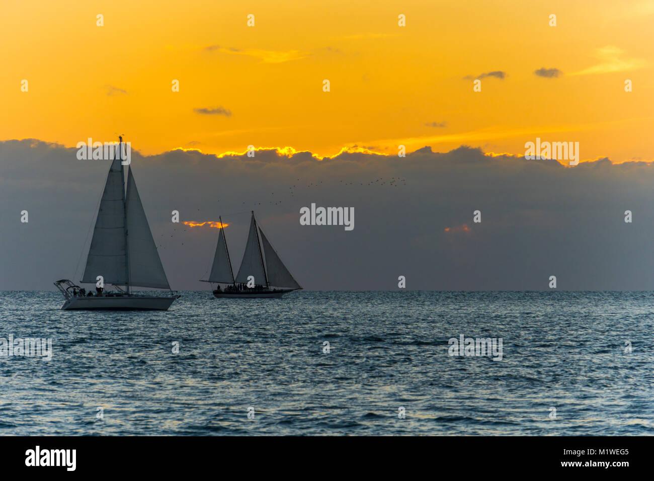 Stati Uniti d'America, Florida, arancione tramonto dietro le nuvole a key west con due barche a vela in acqua Immagini Stock