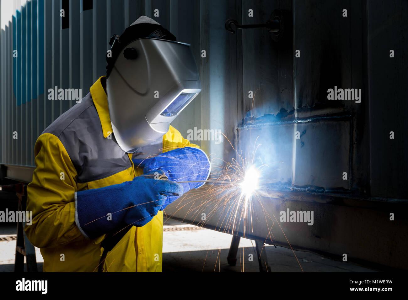 L'industria lavoratore con acciaio di saldatura per la riparazione di strutture di contenitore fabbricazione Immagini Stock
