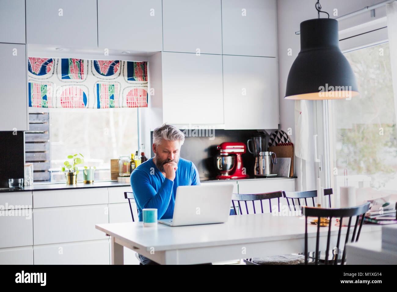 Uomo con notebook in cucina Immagini Stock