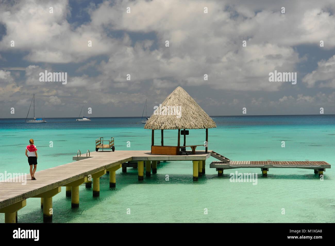 Donna che cammina su un molo a Bora Bora Immagini Stock