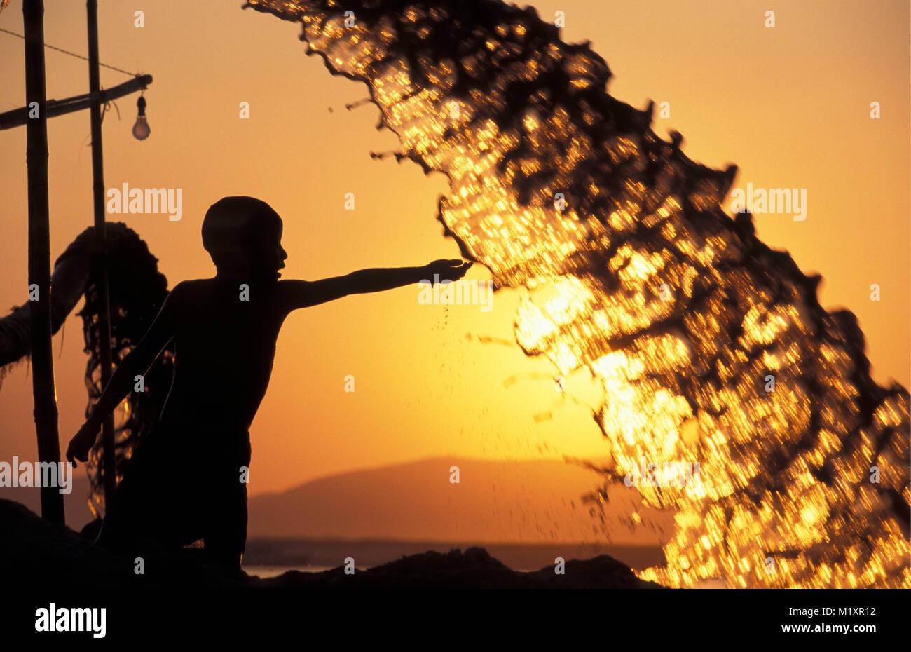 Myanmar (Birmania). Mandalay. Ayeyarwady Irradwaddy (fiume). Ragazzo giocando con l'acqua. Silhouette. Il tramonto. Immagini Stock
