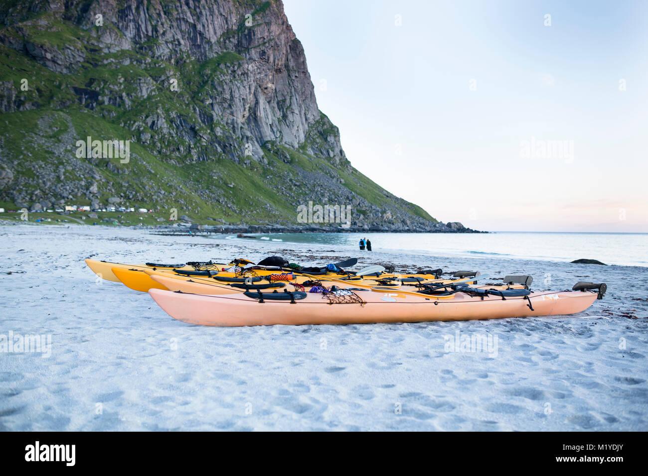 Cinque kayak nella sabbia in spiaggia un po' dall'oceano a Isole Lofoten in Norvegia. Foto Stock