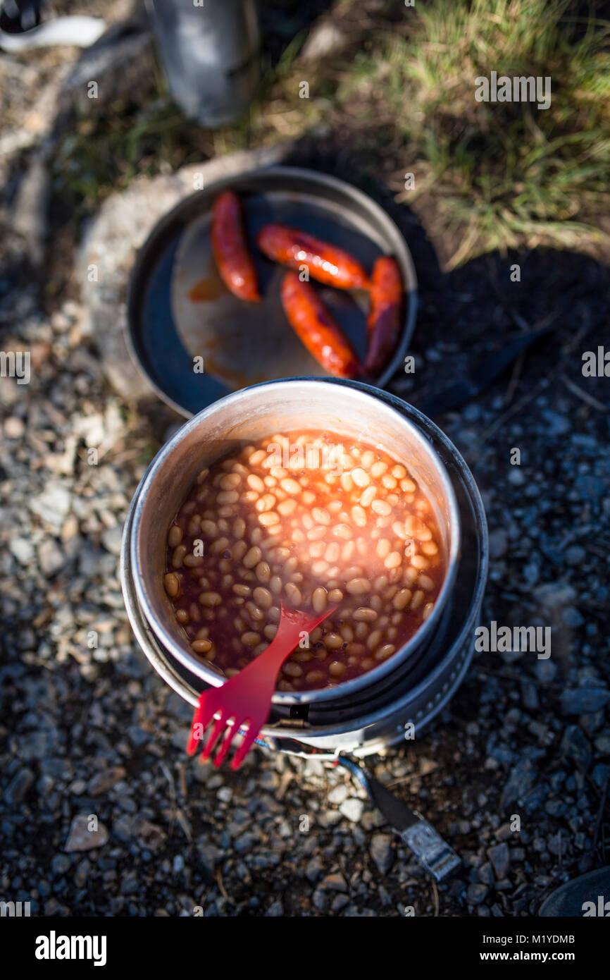 Fagioli al forno in un tegame e salsicce in una padella su un campeggio cucina sulla terra. In parte sun e in parte Immagini Stock