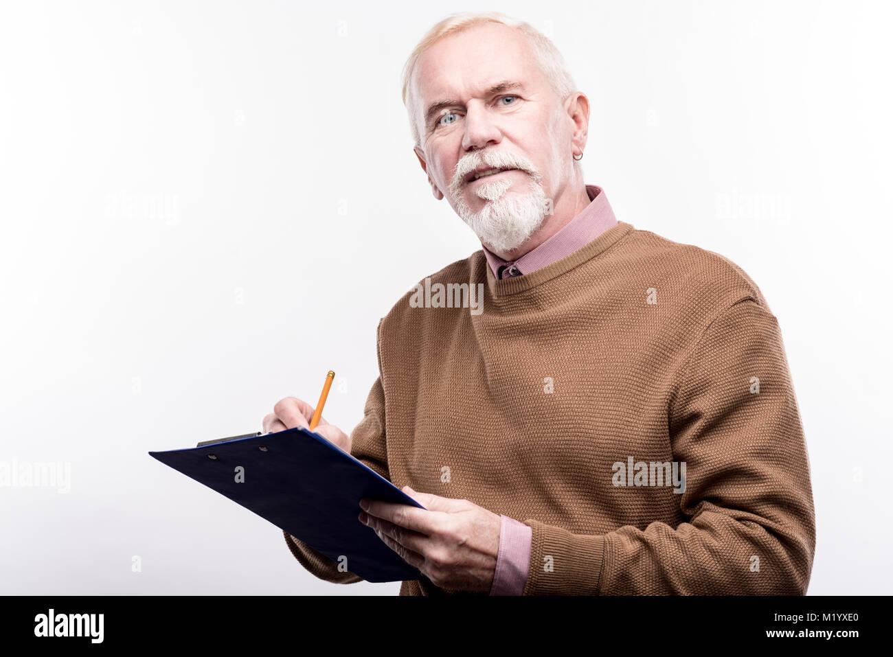 Piacevole uomo senior la compilazione di moduli sul supporto per fogli Immagini Stock