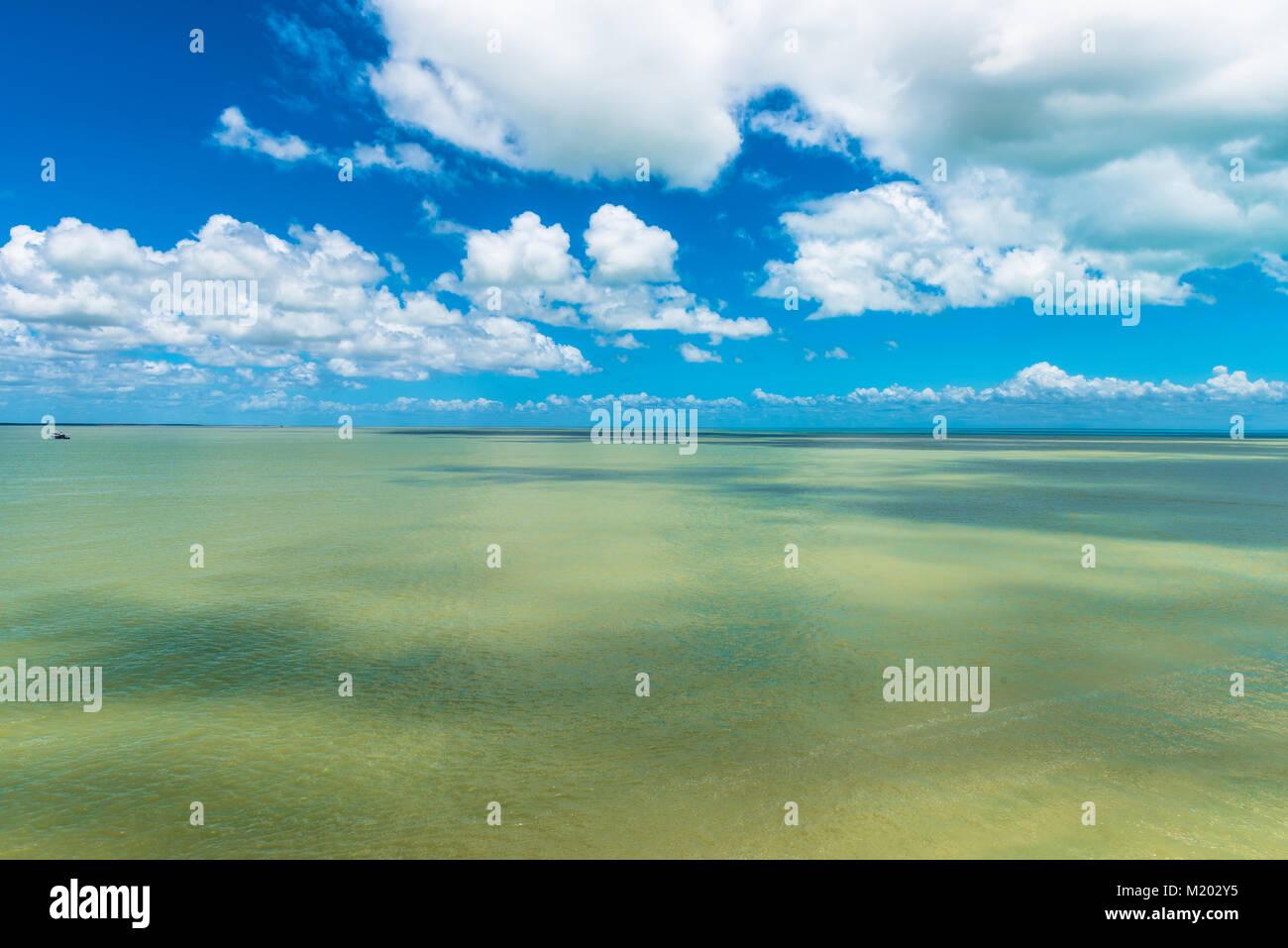 Piccola barca a sinistra dall'orizzonte fornisce la prospettiva contro il vasto mare e cielo Immagini Stock