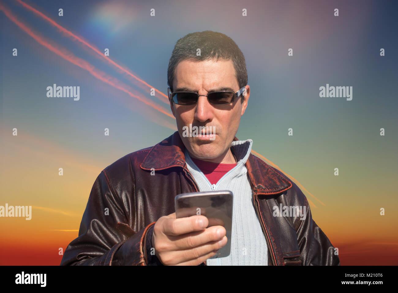 Di mezza età uomo caucasico, vestiti casual, la lettura di un messaggio appena ricevuto sul suo smartphone. Vita Foto Stock
