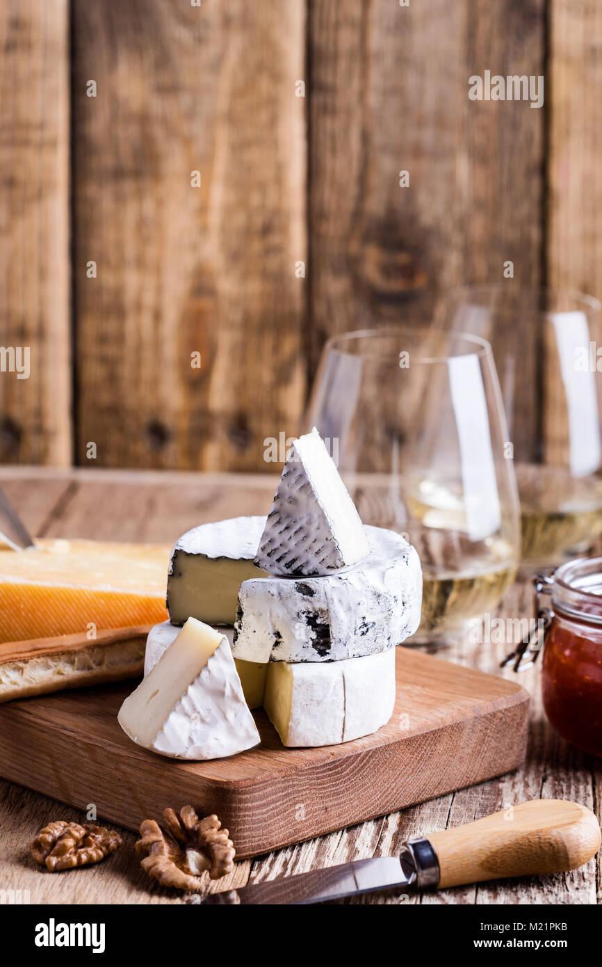Scheda con diversi tipi di formaggio su tavola in legno rustico Immagini Stock