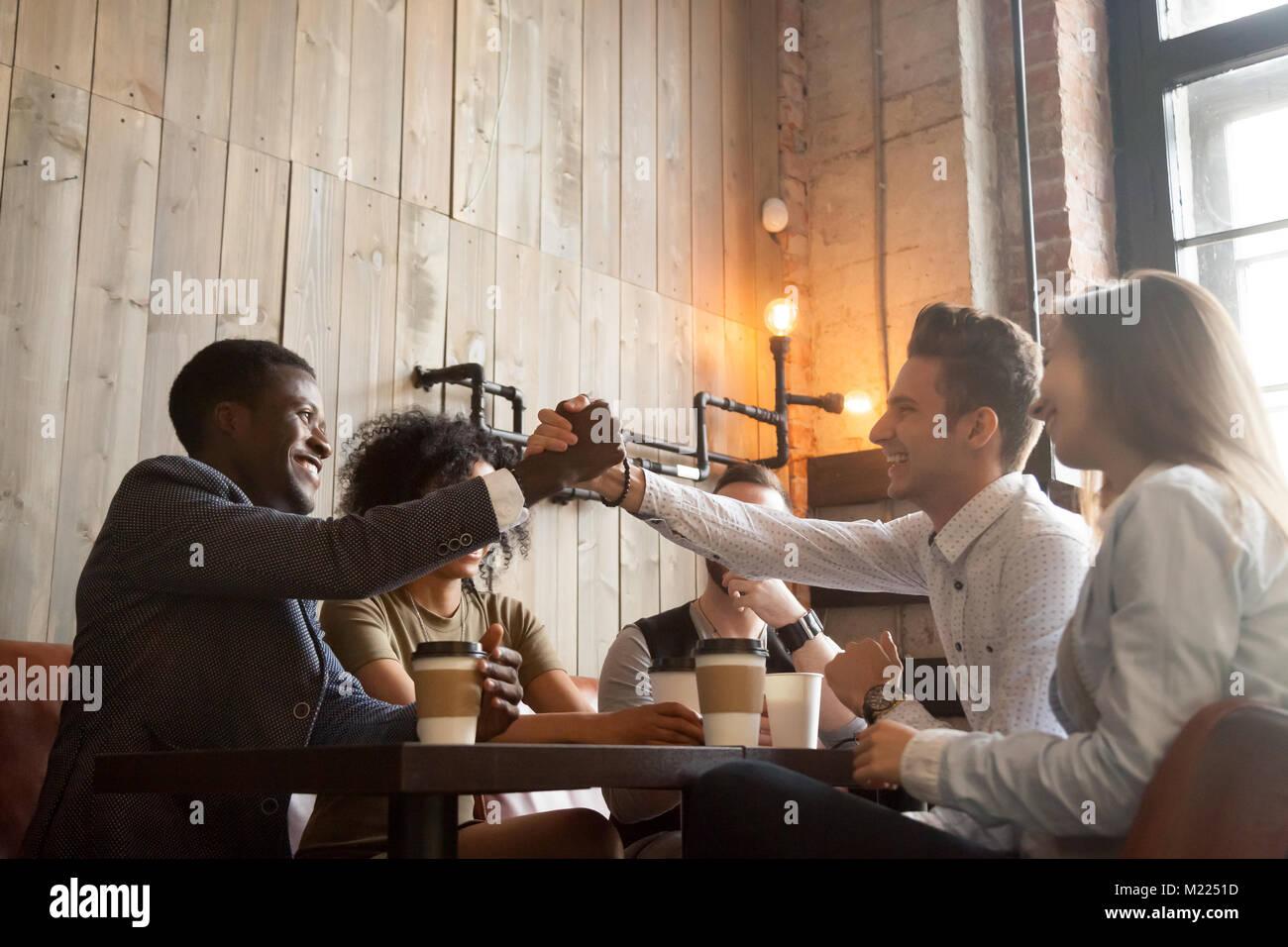 Africani e caucasici handshaking gli uomini a coffeehouse incontro wit Immagini Stock