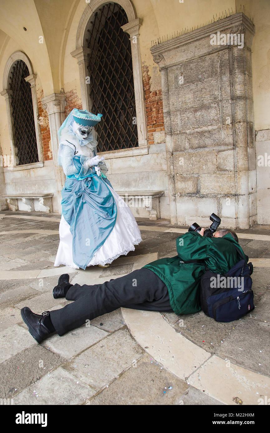 Fotografo è scattare foto della maschera Veneziana sdraiato sul pavimento con la fotocamera reflex digitale, Immagini Stock