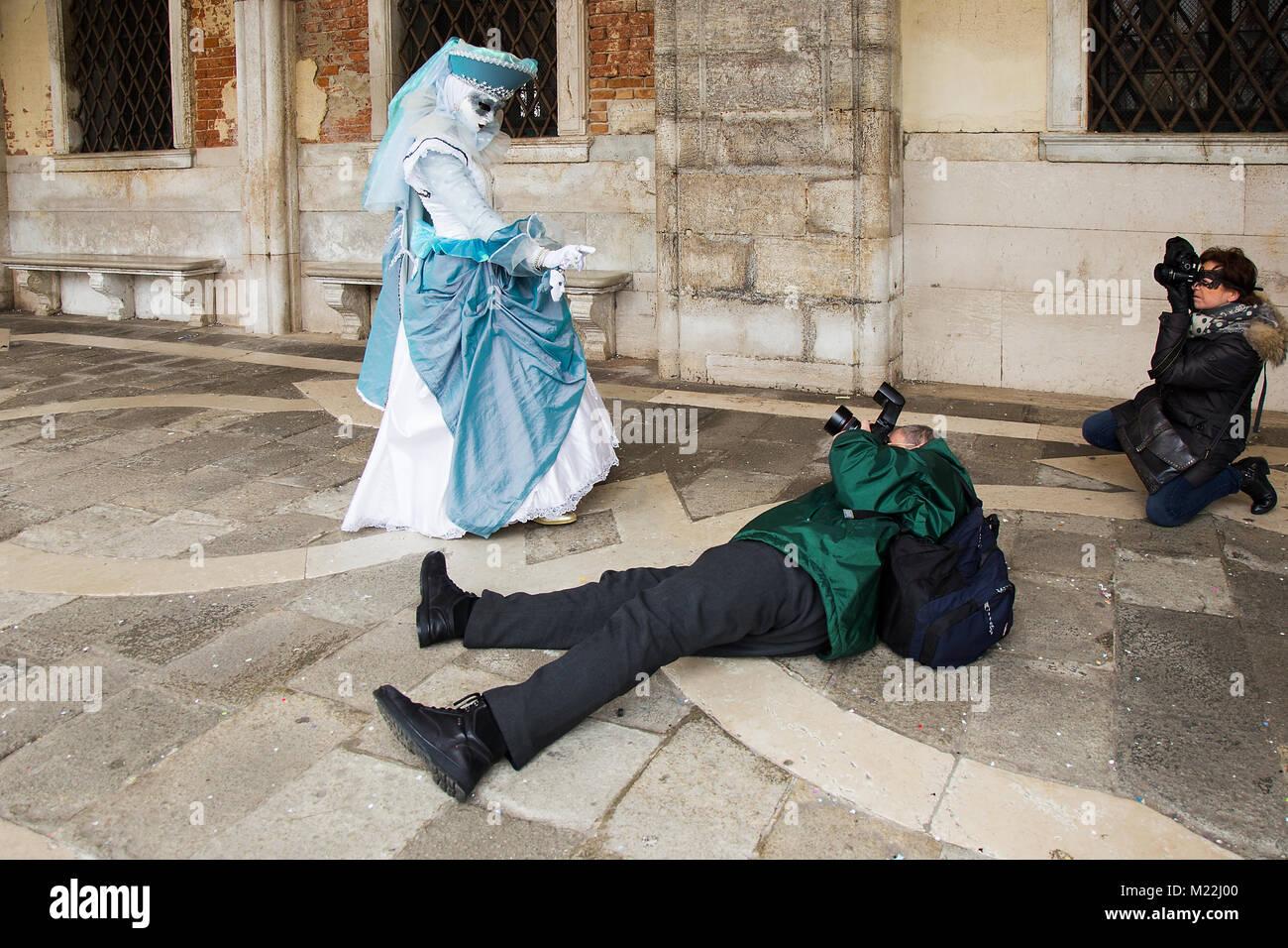 Il Carnevale di Venezia - Fotografo è scattare foto della maschera Veneziana sdraiato sul pavimento con la Immagini Stock