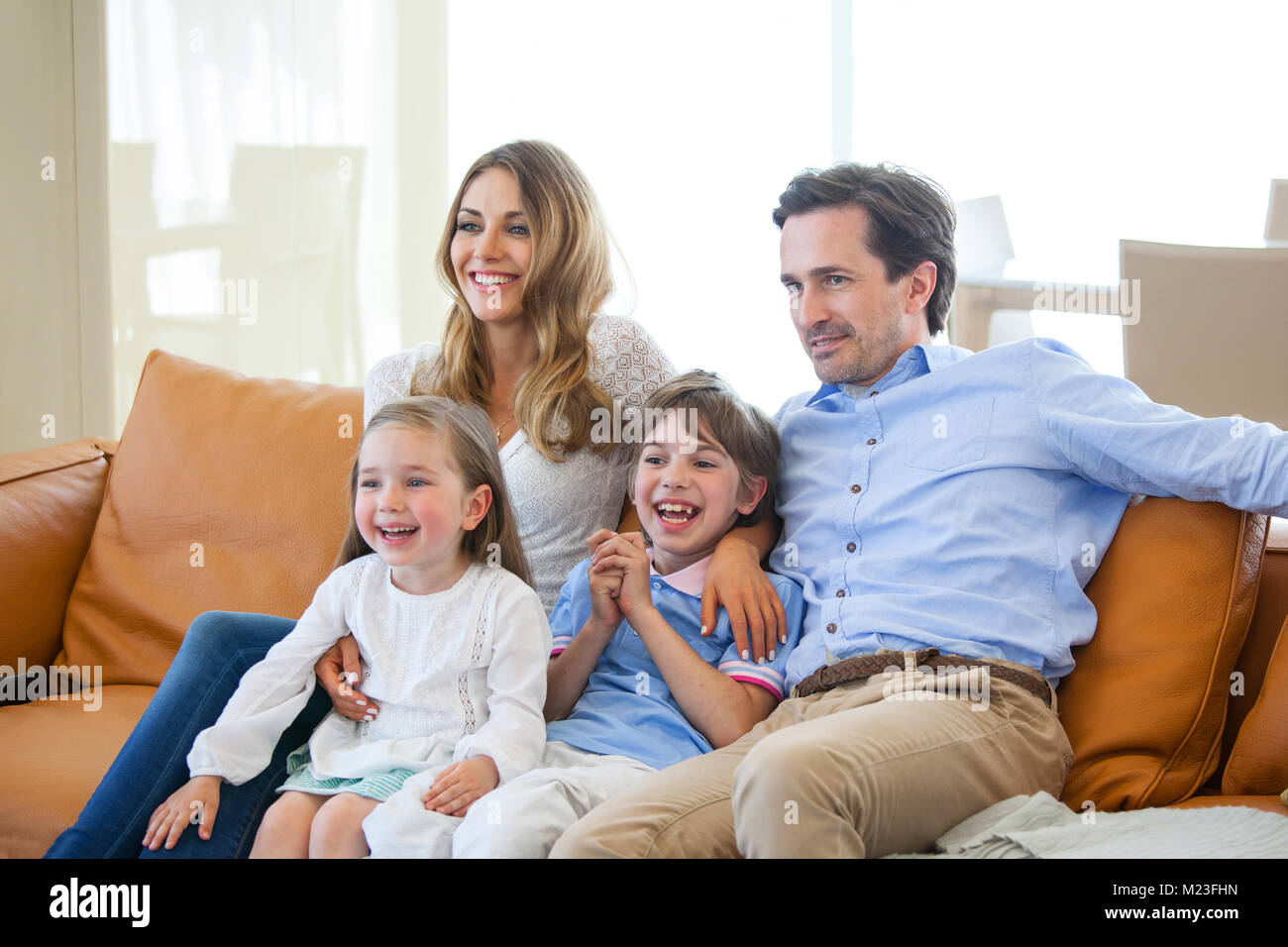 Adorabili e famiglia con due bambini di guardare la tv in soggiorno ...