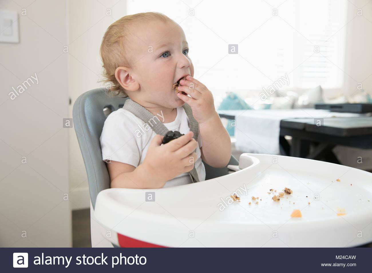 Confuso baby boy eating in sedia alta Immagini Stock
